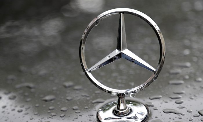 The logo of German car manufacturer Mercedes-Benz is rain covered at a car in Munich, Germany, on July 28, 2017. (AP Photo/Matthias Schrader)