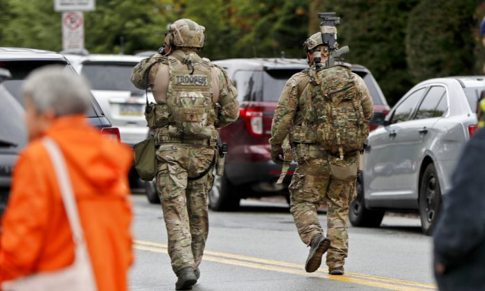 Armed law enforcement officers walk through the street in the Squirrel Hill neighborhood of Pittsburgh where a shooter opened fire during services at the Tree of Life Synagogue on Oct. 27, 2018. (AP/Keith Srakocic)
