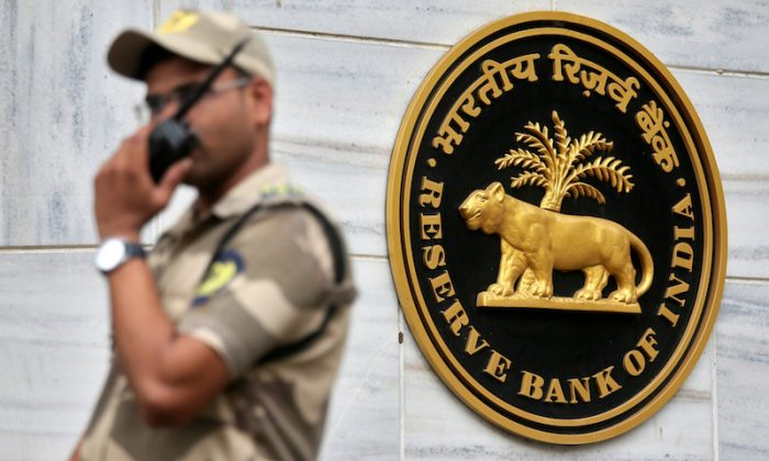 A guard stands next to the Reserve Bank of India (RBI) logo outside its headquarters in Mumbai, India, Oct. 5, 2018. (Reuters/Francis Mascarenhas)