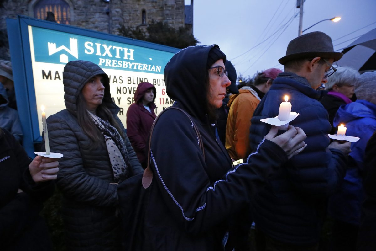 people hold candles for the victims of the Pittsburgh shooting