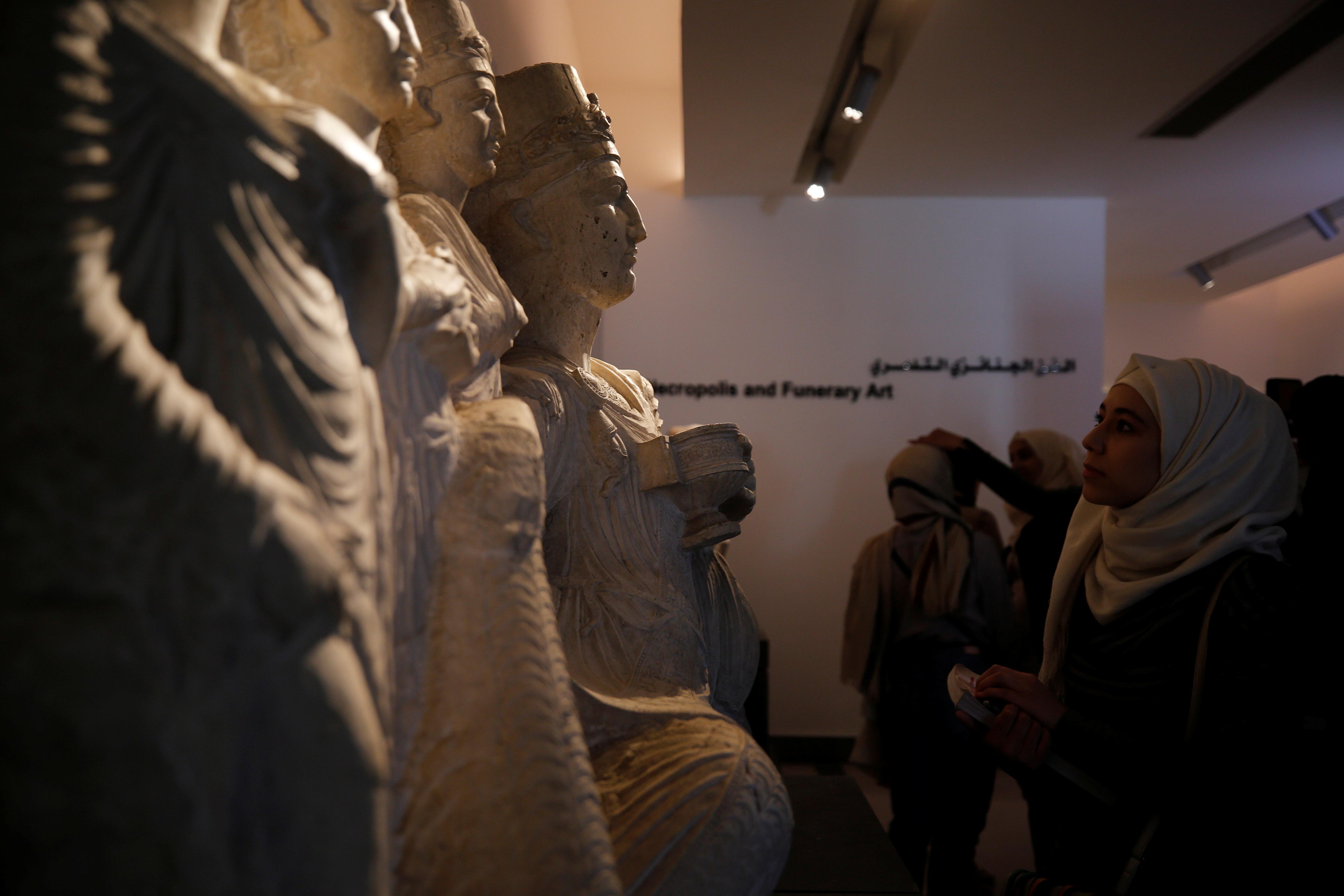 Visitors look sculptures displayed