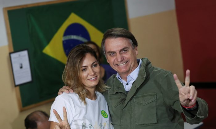 Jair Bolsonaro, newly elected president of Brazil, poses with his wife Michelle as they arrive to cast their votes at a polling center in Rio de Janeiro, Brazil Oct. 28, 2018. (Reuters/Ricardo Moraes/Pool)