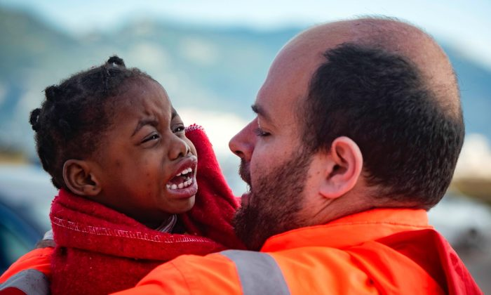 A child is carried by a member of Spain's Maritime Rescue Service as they arrive at the port of San Roque, southern Spain, on Oct. 27, 2018. (Marcos Moreno/AP)