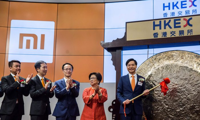 Xiaomi founder, chairman and CEO, Lei Jun (R), hits a gong at the company's initial public offering (IPO) launch on the Hong Kong Stock Exchange in Hong Kong on July 9, 2018. (ISAAC LAWRENCE/AFP/Getty Images)