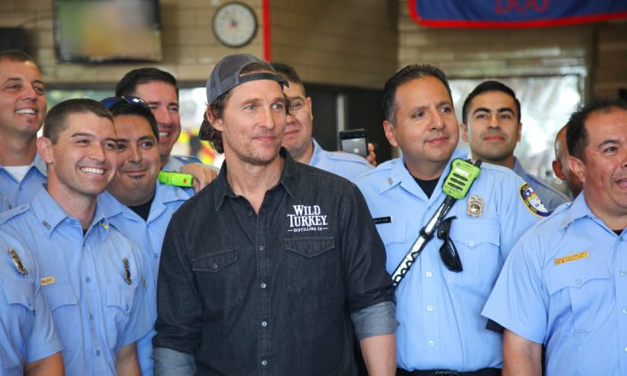 Matthew McConaughey posing with first responders in Houston as he surprised them with catered lunches on Oct. 28, 2018. (AP Photo/John Mone)