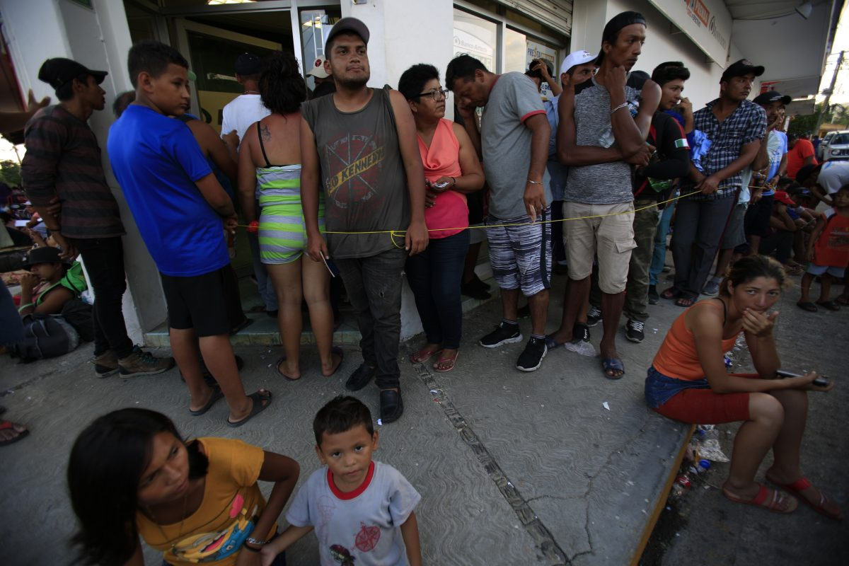 Migrants wait slow moving line