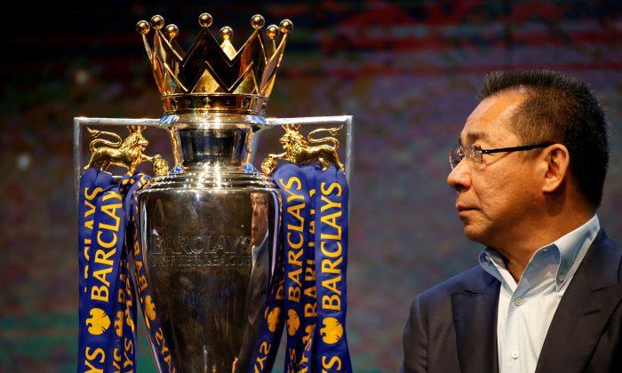 Vichai Srivaddhanaprabha, owner of football club Leicester City, stands on stage next to the club's English Premier League trophy during a meeting with the media in Bangkok, Thailand May 18, 2016. (Jorge Silva/Reuters)