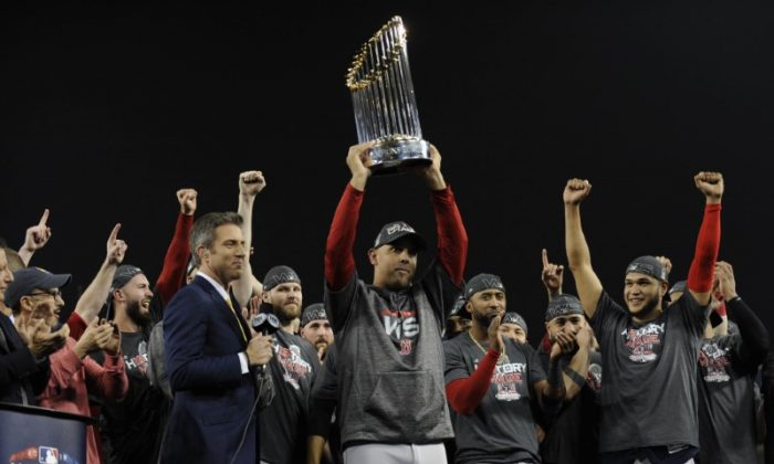 Boston Red Sox manager Alex Cora hoists the Commissioner's Trophy after defeating the Los Angeles Dodgers in game five of the 2018 World Series at Dodger Stadium in Los Angeles, on Oct. 28, 2018. (Gary A. Vasquez/USA TODAY Sports)