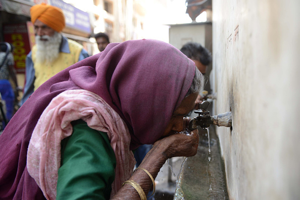 An Indian woman drinks water from a tap on March 22, 2018.