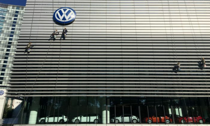 Workers clean the facade of a car showroom under a Volkswagen logo on the Chinese National Day in Beijing, China on Oct. 1, 2018. (Stringer/Reuters)