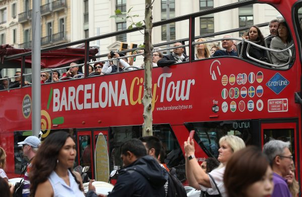 Tourists ride a double-decker bus on Passeig de Gracia avenue in Barcelona