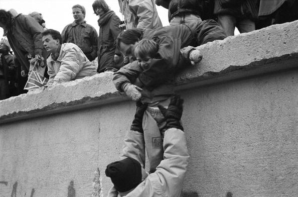East Berliners climb onto the Berlin Wall to celebrate the effective end of the city's partition, on Dec. 31, 1989.   Steve Eason/Hulton Archive/Getty Images