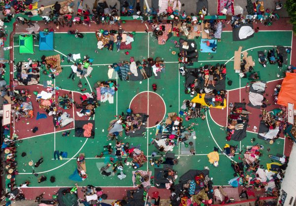 Honduran migrants heading in a caravan to the US, resting in a basketball pitch in San Pedro Tapanatepec, Oaxaca state, southern Mexico