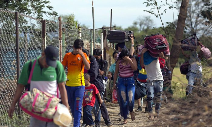 "Venezuelan migrants hide their faces as they cross illegally into Colombia along a path known as a ""trocha"" on Aug. 31, 2018. Millions have fled Venezuela's deadly food shortages and spiralling hyperinflation, demonstrating the resounding failure of two successive socialist governments. (AP Photo/Ariana Cubillos)"