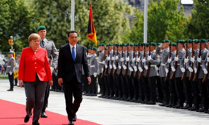 German Chancellor Angela Merkel and Chinese Prime Minister Li Keqiang review the guard of honor at the chancellery in Berlin on July 9, 2018. (Fabrizio Bensch/Reuters)