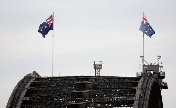 The Australian flag (R) and the New Zealand flag fly on the Sydney Harbour Bridge
