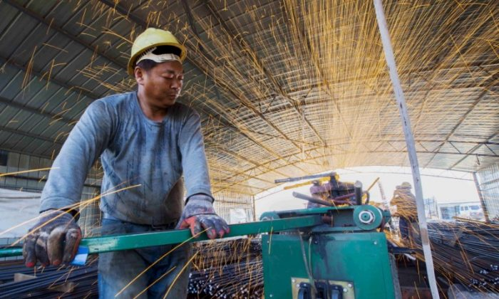 A laborer cuts steel bars at a railway bridge construction site in Lianyungang, Jiangsu Province, China on Sept. 12, 2015. (China Daily/Reuters)