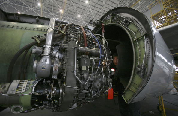 An aircraft technicians checks the engine of an airplane at the Chongqing Airport in Chongqing, China, on Feb 5, 2007. (China Photos/Getty Images)