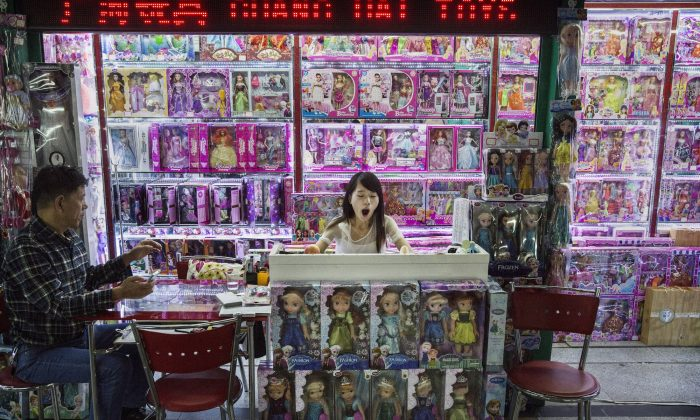 A Chinese trader yawns as she waits on customers at her stall selling wholesale dolls at the Yiwu International Trade City in Yiwu County, Zhejiang Province, on Sept. 24, 2015. (Kevin Frayer/Getty Images)