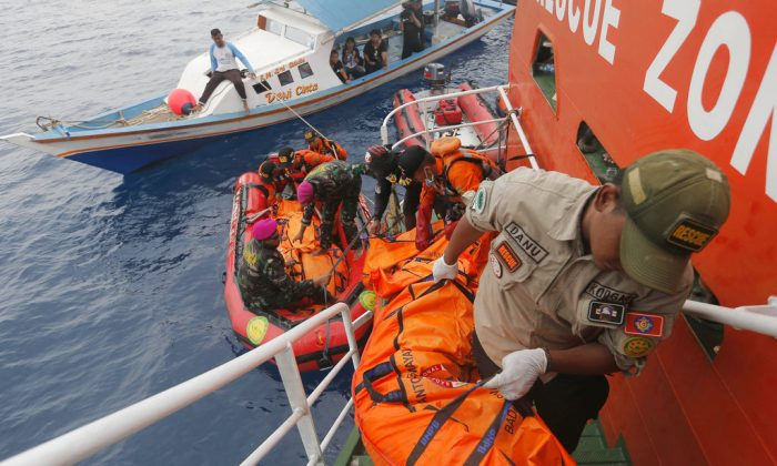 Rescuers load body bags containing debris and remains of the victims of the crashed Lion Air plane during a rescue operation in the waters of Tanjung Karawang, Indonesia, Oct. 30, 2018. (AP Photo/Tatan Syuflana)
