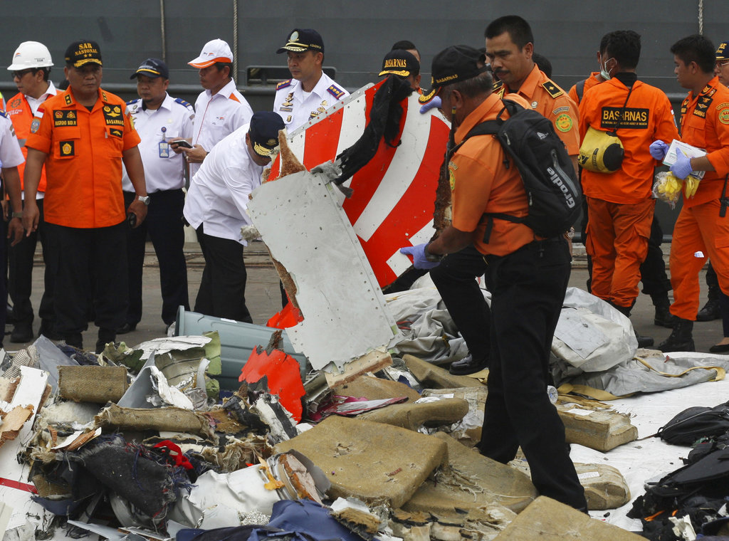 A rescuer inspects a part of Lion Air plane retrieved from the waters