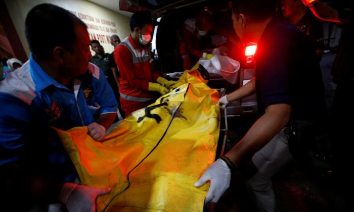 Officials carry a body bag off an ambulance to be identified by Indonesian Disaster Victim Identification (DVI) officer at Bhayangkara R. Said Sukanto hospital in Jakarta, Indonesia, Oct. 30, 2018. (Reuters/Willy Kurniawan)