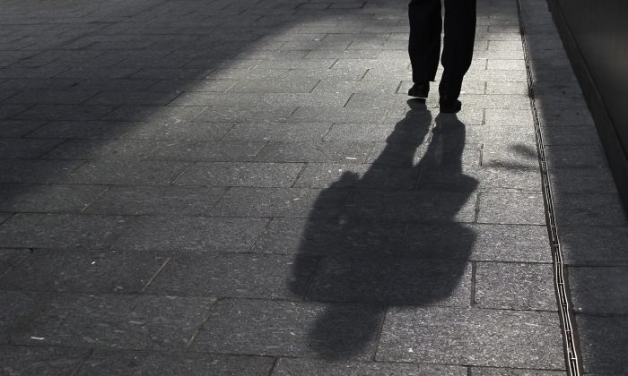 A man casts a shadow in London's financial district on Oct. 7, 2011. (Reuters/Olivia Harris)