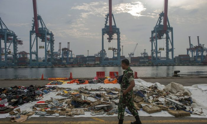 An Indonesian soldiers walk past debris retrieved from the waters where Lion Air flight JT 610 is believed to have crashed at Tanjung Priok Port in Jakarta, Indonesia, Oct. 31, 2018. (AP Photo/Fauzy Chaniago)
