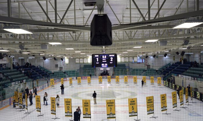 Sixteen banners in honour of the lives taken in the April bus crash are shown in the foreground and the banners for the survivors sit in the background during a tribute to the Humboldt Broncos in Humboldt, Sask., on Sept. 12, 2018. (Jonathan Hayward/The Canadian Press)