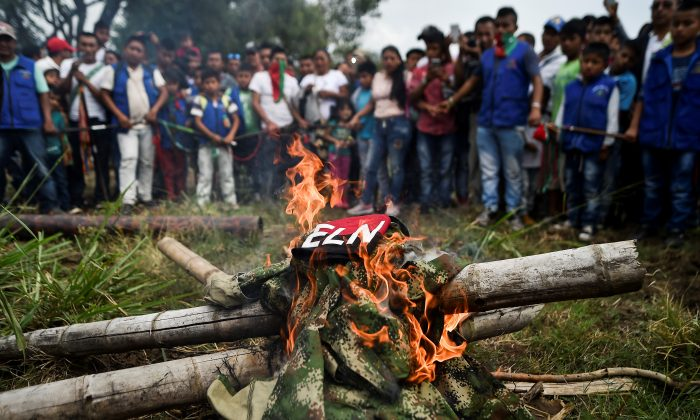 Indigenous people of the Nasa ethnic group burn uniforms seized from ELN guerrillas on July 6, 2018, in Corinto, Cauca department, Colombia. (Luis Robayo/AFP/Getty Images)