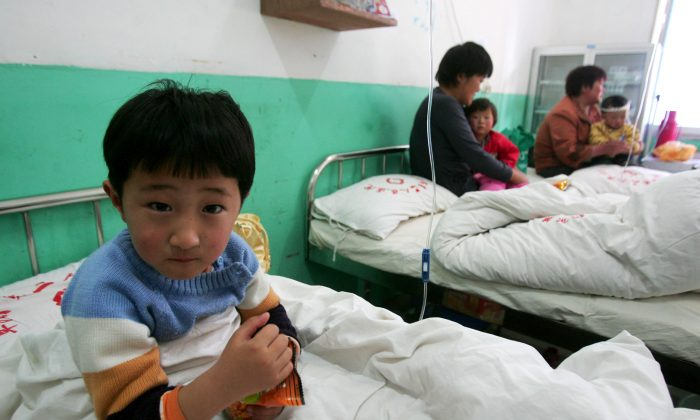 A young girl who suffers from the hand, foot and mouth disease undergoes treatment at a hospital in Fuyang City, Anhui Province, China, on April 28, 2008. (China Photos/Getty Images)