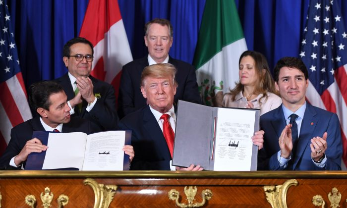 Mexico's President Enrique Pena Nieto (L), U.S. President Donald Trump (C) and Canadian Prime Minister Justin Trudeau, sign the new North American trade agreement in Buenos Aires, on the sidelines of the G20 Leaders' Summit on Nov. 30, 2018. (Saul Loeb/AFP/Getty Images)