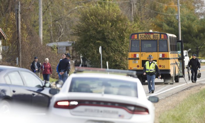 Emergency personnel responded to a scene of a collision that killed three children crossing SR 25 as they were boarding their school bus north of Rochester, Indiana, on Oct. 30, 2018. (Santiago Flores/South Bend Tribune via AP)