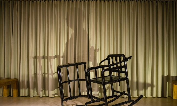 """This photo illustration shows the shadow of a person and a 'tiger chair', a restraining chair reportedly used by Chinese authorities when questioning detainees, on a stage in Hong Kong on Nov. 2, 2018. An art show by Chinese political cartoonist Badiucao, whose real-time image was going to be projected onto an avatar sitting in the chair, was cancelled due to safety concerns with organizers citing """"threats made by Chinese authorities relating to the artist."""" (Anthony Wallace/ AFP/Getty Images)"""