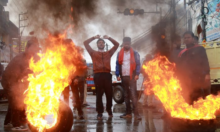 Demonstrators shout slogans next to burning tyres during a protest against the killing of a leader of India's ruling Hindu nationalist Bharatiya Janata Party's (BJP), and his brother by unidentified gunmen in Kishtwar town, in Jammu, on Nov. 2, 2018. (Mukesh Gupta/Reuters)