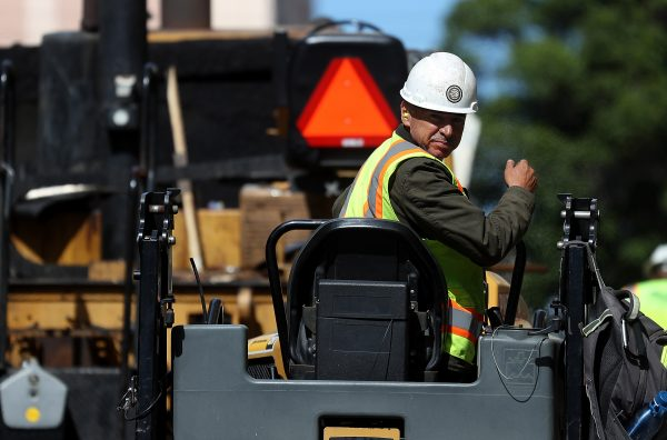 A construction worker operates a steam roller while paving a road on in San Francisco