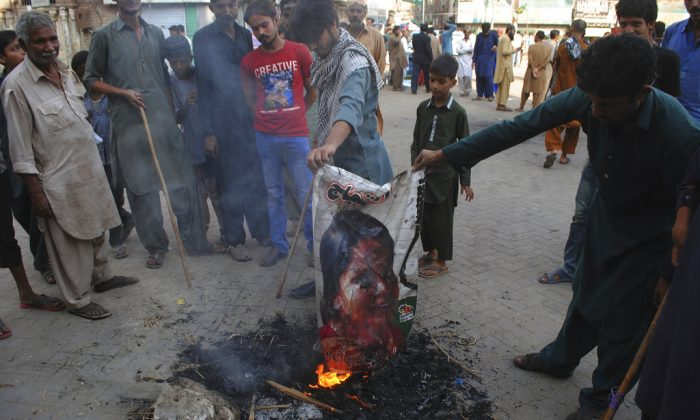 Pakistani protesters burn a poster image of Christian woman Asia Bibi, who has spent eight-years on death row accused of blasphemy and acquitted by a Supreme Court, in Hyderabad, Pakistan, Nov. 1, 2018. (AP Photo/Pervez Masih