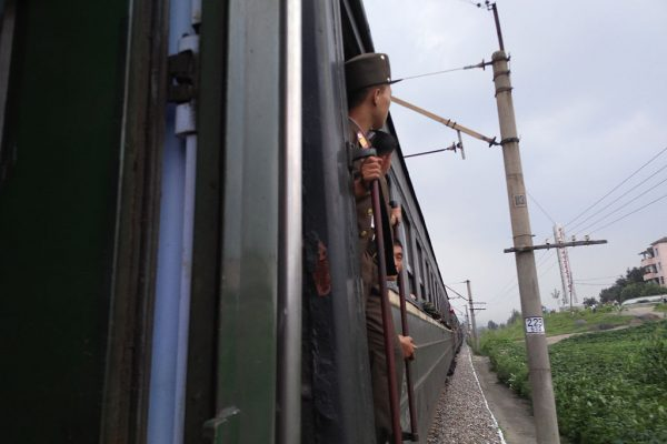 North Korean soldier looks out from train during a train journey