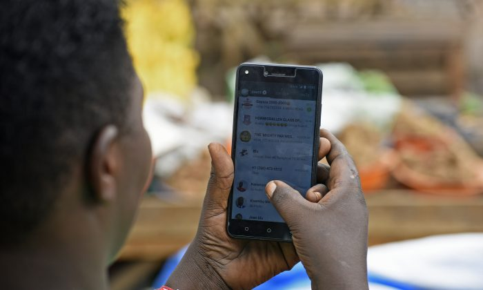 A woman uses WhatsApp on her phone in Kampala, Uganda, on July 5, 2018. (Isaac Kasamani/AFP/Getty Images)