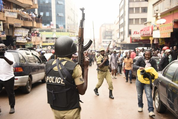 Ugandan police officers lift their AK-47 riffle during demonstrations in Kampala, Uganda.