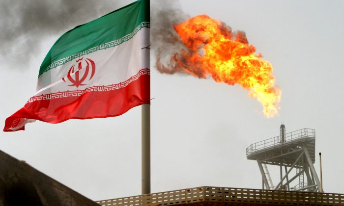 A gas flare on an oil production platform in the Soroush oil fields is seen alongside an Iranian flag in the Persian Gulf, Iran, on July 25, 2005. (Raheb Homavandi/Reuters)