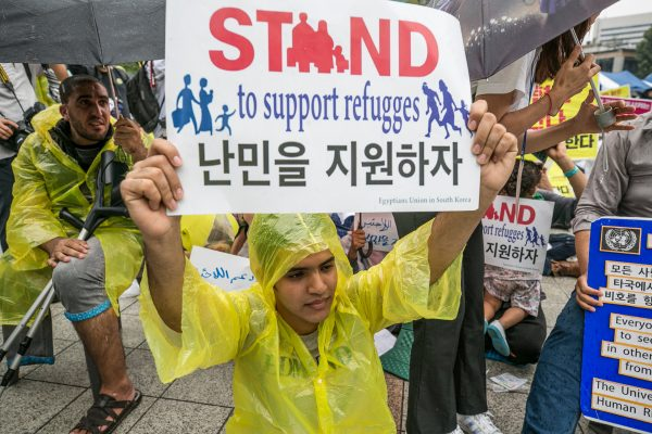 Activists hold signs in support of Yemeni asylum seekers in South Korea.