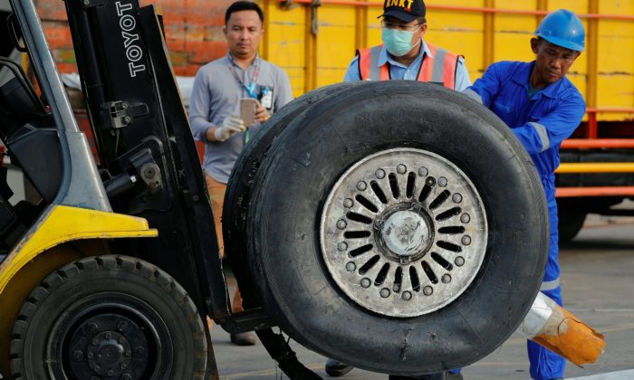 A worker assists his colleague as a tyre from Lion Air flight JT610 is lifted up at Tanjung Priok port in Jakarta, Indonesia, on Nov. 4, 2018. (Beawiharta/Reuters)