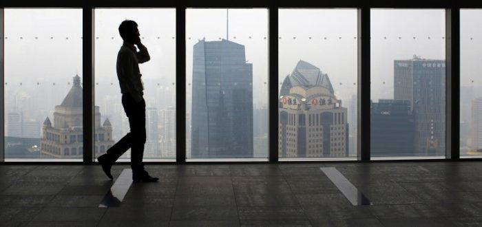 A man talks on a mobile phone as he walks past the view of the Shanghai skyline in China on Sept. 4, 2014. (Carlos Barria/Reuters)