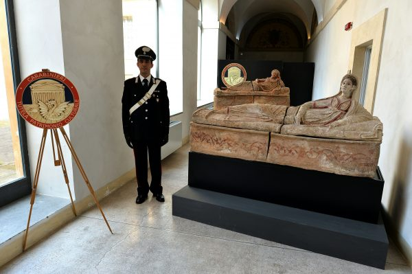 A carabiniere stands next to recovered archaeological artifacts