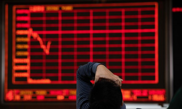 An investor gestures as he looks at stock price movements on a screen at a securities company in Beijing on October 12, 2018. (NICOLAS ASFOURI/AFP/Getty Images)