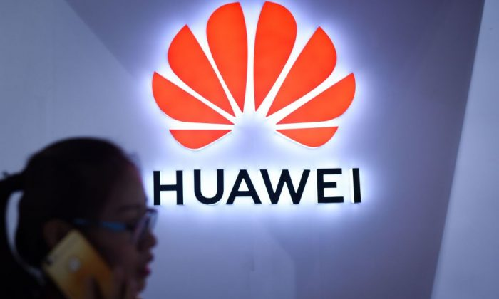 A woman uses her mobile phone in front of a LED display board of Huawei at Beijing International Consumer Electronics Expo in Beijing on July 9, 2018. (Wang Zhao/AFP/Getty Images)