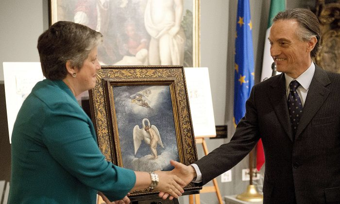 """U.S. Secretary of Homeland Security Janet Napolitano and Italian Ambassador to the U.S. Claudio Bisogniero unveil a Renaissance painting by Lelio Orsi called """"Leda and the Swan"""" during a repatriation ceremony in Washington DC on April 26, 2012. (Jim Watson/AFP/Getty Images)"""