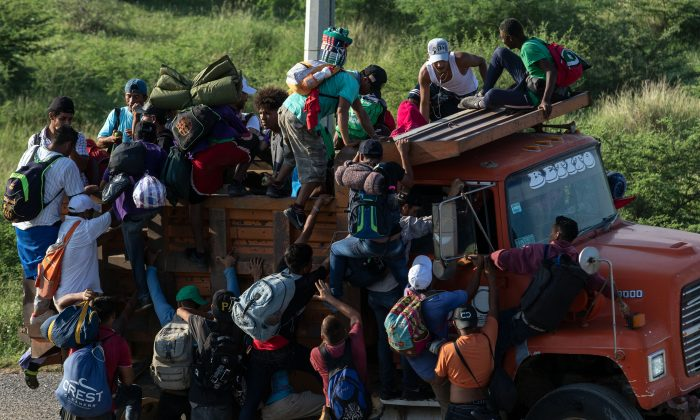 Migrants in a caravan heading to the United States climb on a truck on the road from La Ventosa to Matias Romero, Oaxaca State, Mexico, on Nov. 1, 2018. (Guillermo Arias/AFP/Getty Images)