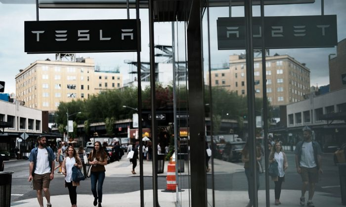 People walk by a Tesla showroom in the Meatpacking district in Manhattan on Jun. 6, 2018 in New York City. ( Spencer Platt/Getty Images)